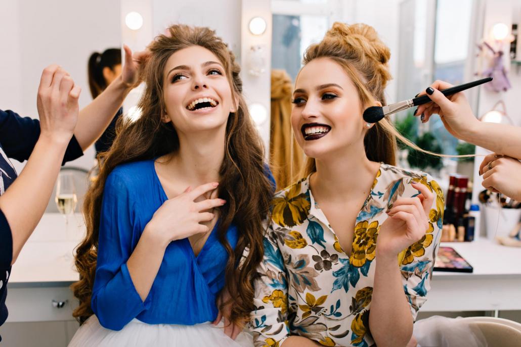Fashion Trends - twee gelukkige meisjes die make-up krijgen